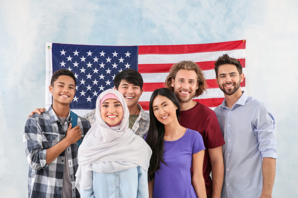 Group of students near wall with USA flag