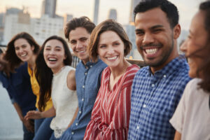 Friends Gathered On Rooftop Terrace For Party With City Skyline In Background