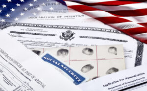 US Certificate of Citizenship, declaration of intention, fingerpirnt card, social security card, application for naturalization and port of arrival manifest with red, white and blue ribbon
