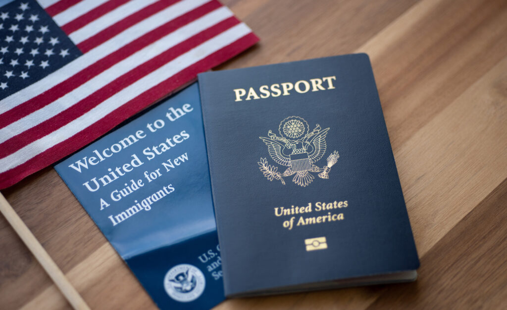 Passport of USA (United states of America) next to a Guide for new Immigrants - Welcome to the United states and American Flag. Wooden Background.